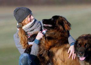 Frau mit Mütze und Schal spielt mit Ihren Hunden
